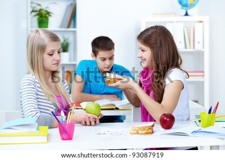 Cute girl offering her friend sandwich during break in college - stock photo