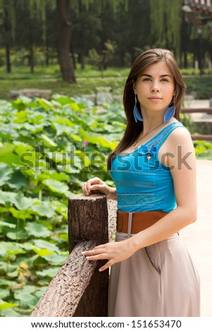 Cute girl on the bridge near pond with pink lotus, young woman walking in the lotus park