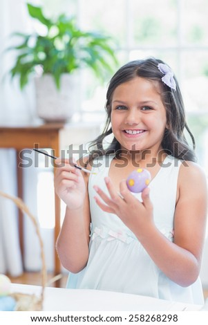 Cute girl painting easter eggs in the living room - stock photo