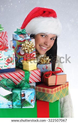 Cute girl peeking around a large stack of Christmas presents. Closeup in vertical format with snowy background.
