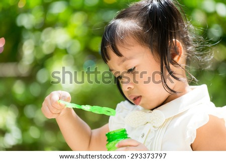Cute girl play with bubble blower