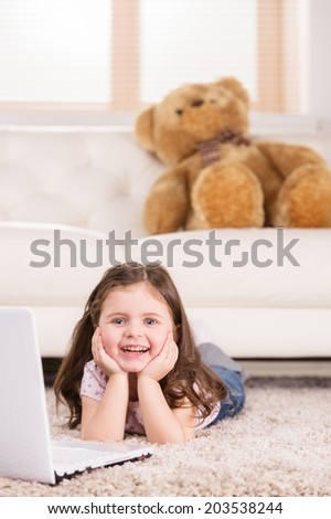 Cute girl playing games on computer. nice girl lying on floor and smiling  - stock photo