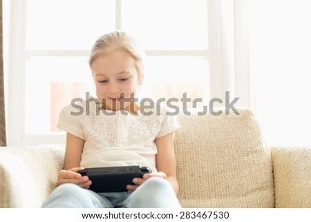 Cute girl playing hand-held video game at home - stock photo
