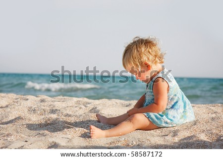 cute girl playing on sand beach - stock photo