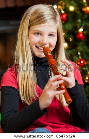 cute girl playing recorder on christmas eve - stock photo