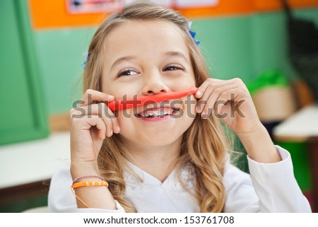 Cute girl playing with clay while looking away in kindergarten - stock photo