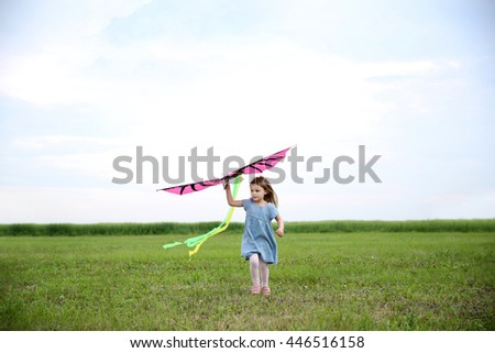 Cute girl playing with kite outdoor - stock photo
