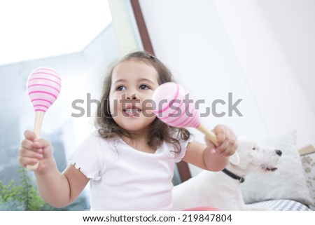 Cute girl playing with maracas while sitting beside dog at home - stock photo