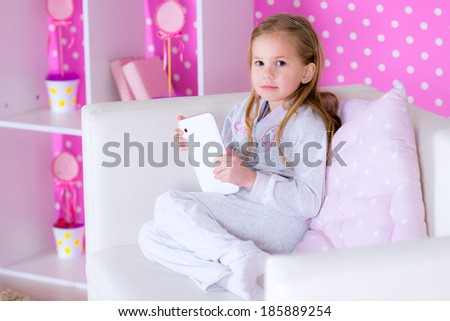 cute girl playing with tablet pc on white sofa - stock photo