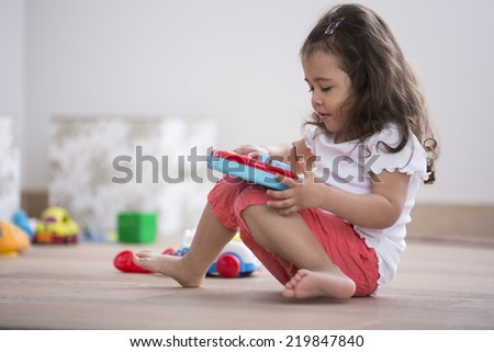 Cute girl playing with toy guitar at home - stock photo