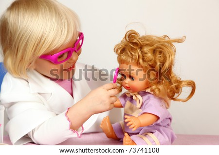 cute girl plays in doctor with doll