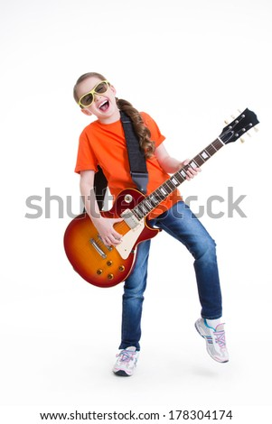 Cute girl plays on the electric guitar with glasses -  isolated on white background.