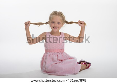 Cute girl plays with her healthy plaited blonde hair. Lovely child holds plaits of hair with her hands and looks in the camera with blue eyes. Childish smile. - stock photo