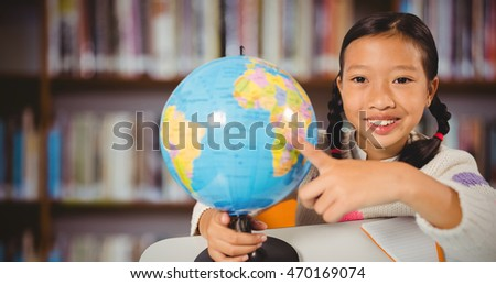 Cute girl pointing on a globe against books on desk in library