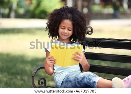 Cute girl reading book on bench