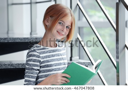 Cute girl reading book on light background