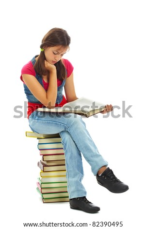 Cute girl reading while sitting on heap of books - stock photo