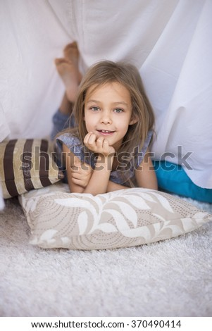 Cute girl resting in her hand made shelter - stock photo