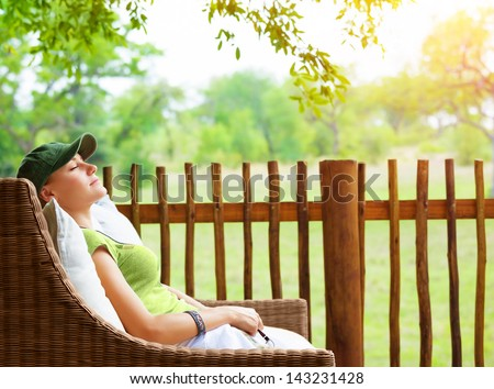 Cute girl resting on veranda, young traveler woman sleeping on backyard in sanatorium, relaxation outdoors, luxury resort, pleasure concept - stock photo