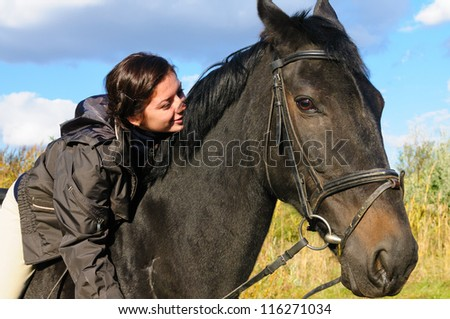 Cute girl riding horse and look at view front of reed - stock photo