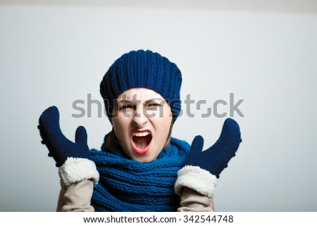cute girl screaming angry, dressed in winter clothes, bright lifestyle photo, isolated on a gray background