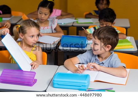 Cute girl showing book to classmate in classroom