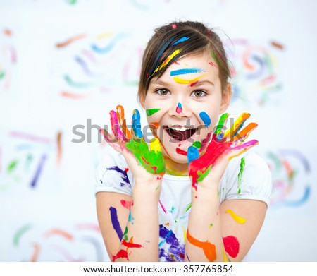 Cute girl showing her hands painted in bright colors - stock photo