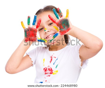 Cute girl showing her hands painted in bright colors, isolated over white - stock photo