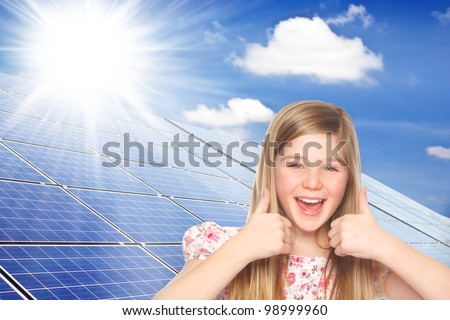 cute girl shows thumbs up for photovoltaic cells - stock photo