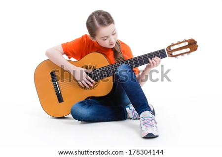 Cute girl sitting and plays on the acoustic guitar -  isolated on white background. - stock photo