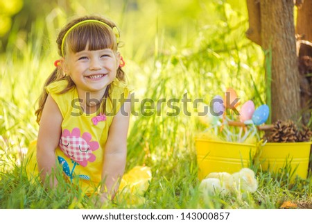 cute girl sitting in the village with her yellow chicken in the bucket