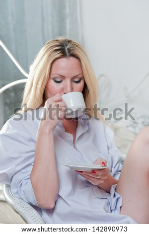 Cute girl sitting on a chair in the bedroom with a cup of coffee