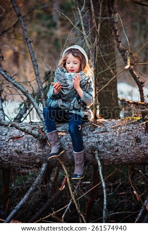 cute girl sitting on old pine tree in early spring forest and playing