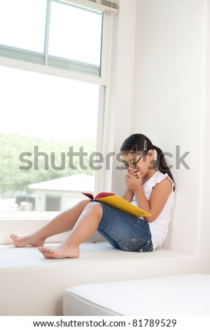 cute girl sitting on window and reading book