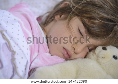 cute girl sleeping in bed with teddy bear - stock photo