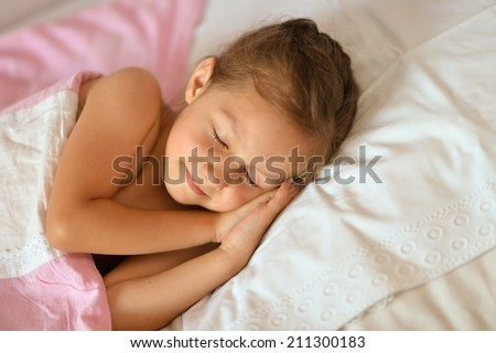 Cute girl sleeping in her bed at home