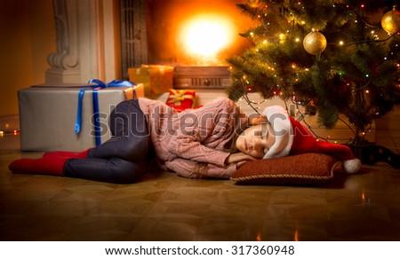 Cute girl sleeping on floor under Christmas tree next to fireplace - stock photo