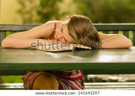 Cute girl sleeping on the table after reading old book.