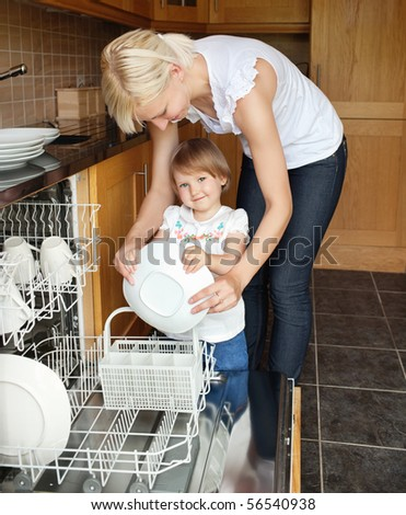 Cute girl smiling in the camera standing besides the dishwasher - stock photo