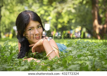 cute girl smiling lying in summer grass, toned image