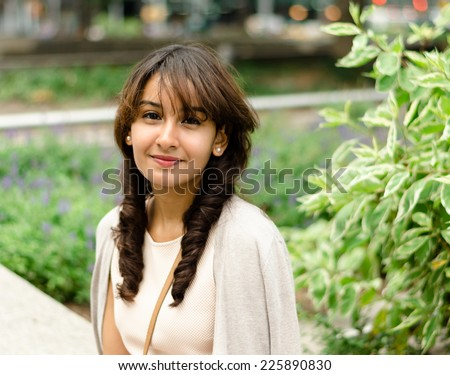 Cute girl smiling outdoors with plants in the background - stock photo