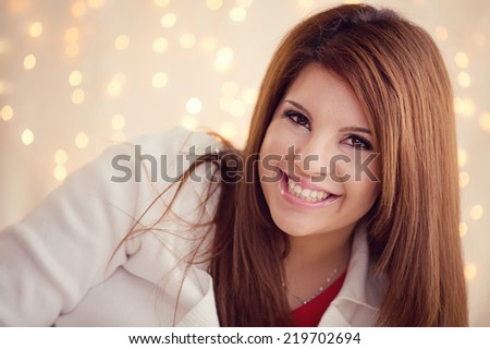 Cute Girl smiling with Christmas lights in the background - stock photo