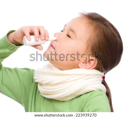 Cute girl spraying her nose with nasal spray, isolated over white - stock photo