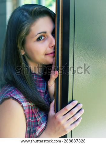 cute girl standing at the open door - stock photo