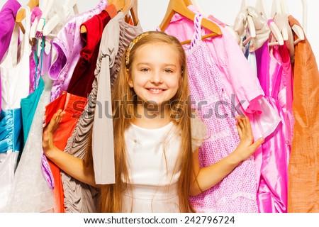 Cute girl standing between hangers during shopping - stock photo