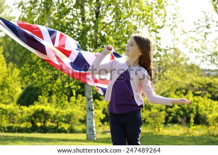 cute girl standing in a park holding a big Britain flag outdoor - stock photo