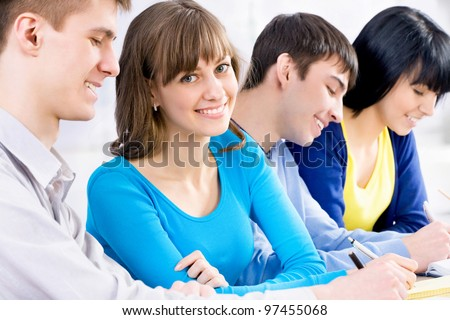 Cute girl student among her friends looking at camera and smiling