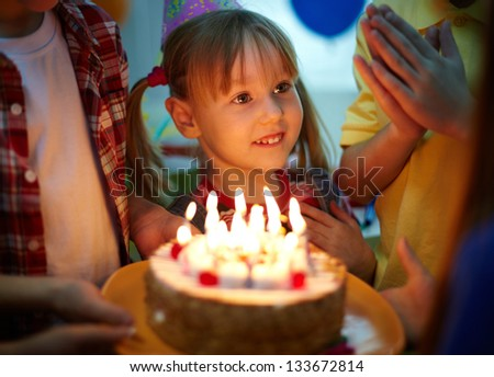 Cute girl surrounded by her friends and birthday cake with candles - stock photo