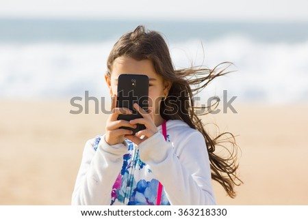 Cute girl taking photo with cellphone on the beach, sea background. - stock photo
