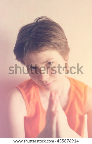 Cute girl teenager in an orange blouse folded her hands in an imploring gesture. Toned - stock photo